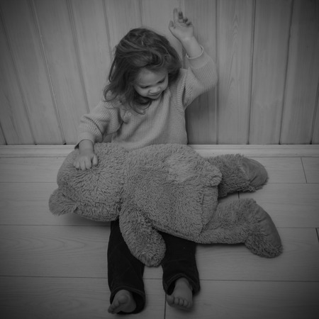girl, child punishes bear toy, pounding, slap Stock Photo