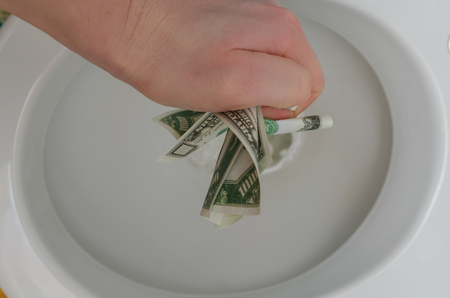 a hand with a thousand dollars over the toilet. Stock fotó