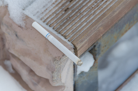 the burnt cigarette lies on the step Stock Photo