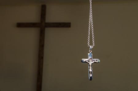 大きな木製の十字架の背景に対する鎖の十字架