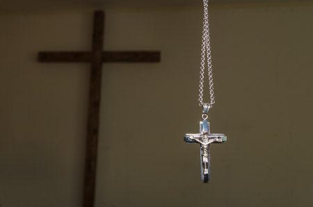 crucifix on a chain against the background of a large wooden cross Stock Photo