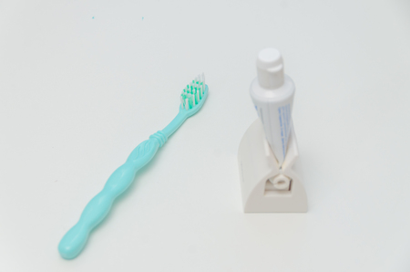 toothbrush and paste on white table