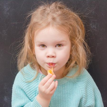 baby girl vegetarian eating a mandarin slice Stock Photo