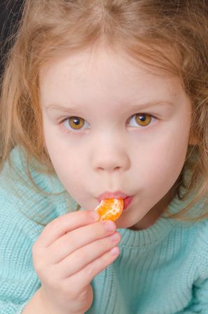 baby girl vegetarian eating a mandarin slice Stok Fotoğraf
