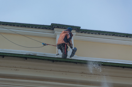 Man worker cleans the roof of the snow, with insurance