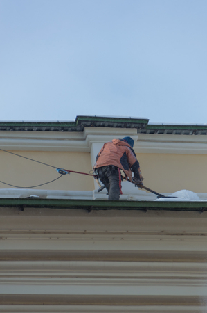 man worker cleans the roof of the snow, with insurance Stock Photo - 96433607