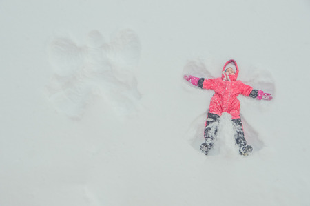Winter girl, baby making angel in the snow, next to the other