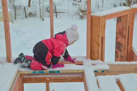 In the winter a brave child, a girl dangerous climbing on the construction of a frame house