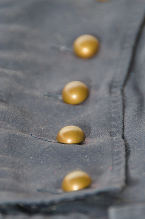 texture, dark blue fabric with brass buttons, cages, background Stock Photo