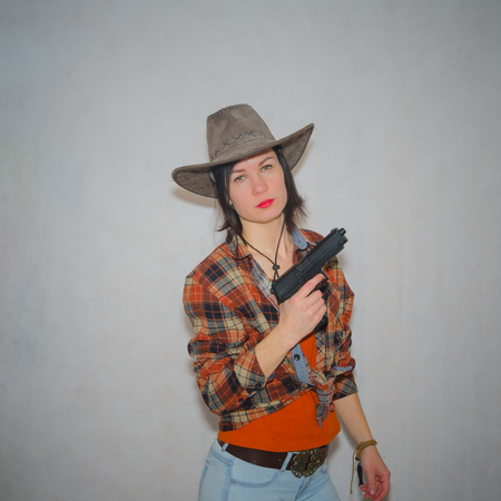 on a gray background, the girl the cowboy with pistol Stock Photo