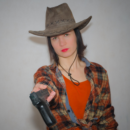 cowboy girl gives a pistol on a gray background Stock Photo