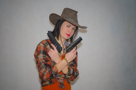 on a gray background, girl cowboy holding two pistols, criss cross