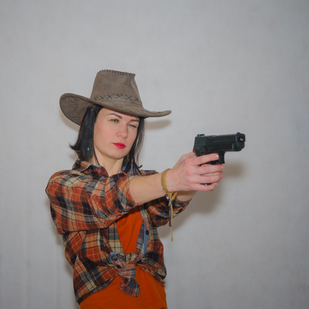 the girl the cowboy with a gun pointing on gray background