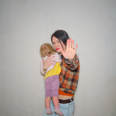 on a gray background, the girl protects the child, hand gesture stop