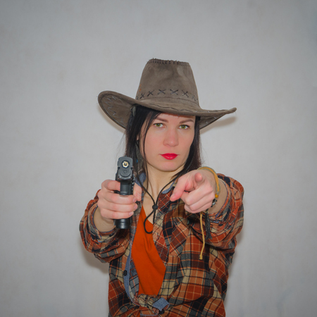 cowboy girl with pistol finger gesture you, on grey background Stock Photo