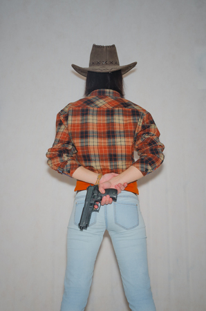 on a gray background, the girl the cowboy with the pistol, standing with her back Stock Photo
