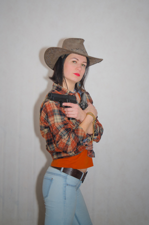 cowboy girl holding two pistols, cross on cross, on grey background