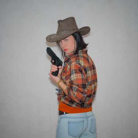 on a gray background, the girl the cowboy with the pistol, standing with her back close up Stock Photo