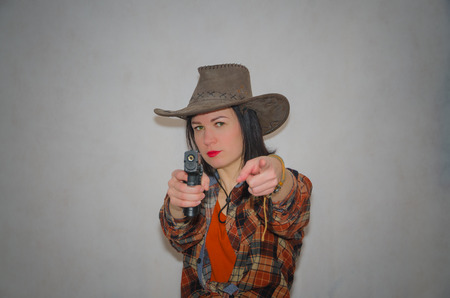 on a gray background, the girl the cowboy with pistol finger gesture you