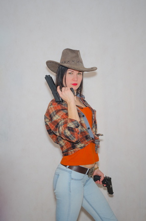 the girl the cowboy with pistol on the grey background