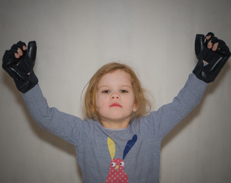 a child, a girl in gloves for hand-to-hand combat raises her hands in a gesture of victory