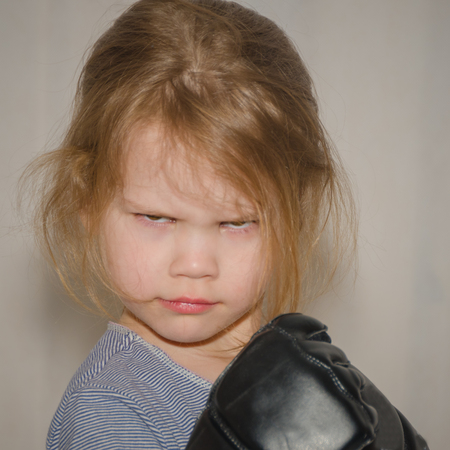 a child, a girl in gloves for hand-to-hand combat in a fighting rack Stock Photo