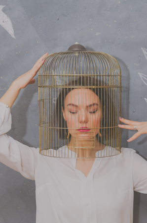 against the background of a gray wall beautiful girl with a bird cage on her head, looked down