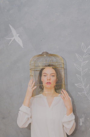 against a gray wall beautiful girl with a bird cage on her head, looking at the camera