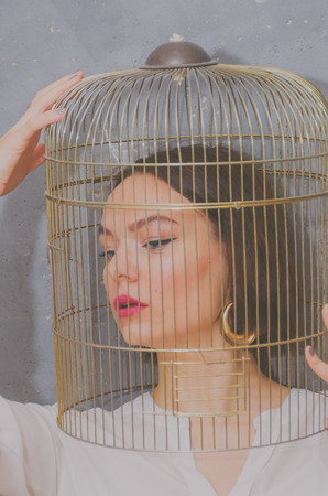 on the background of gray wall beautiful girl with a birdcage on his head Stock Photo