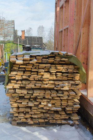 the boards folded in a stack, near the frame house under construction