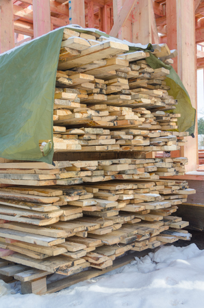the boards folded in a stack, near the frame house under construction Stok Fotoğraf - 98634994