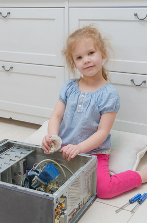 girl, child wipes dust with a cloth before, repairs computer, system unit