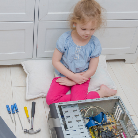 a girl, a child with a screwdriver is preparing to repair the computer system unit Stock Photo