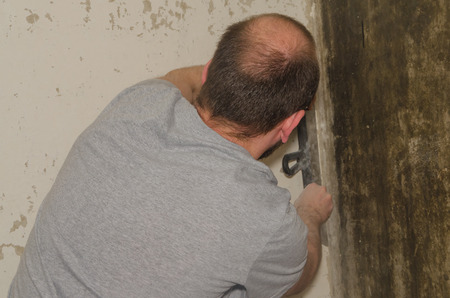male worker with a spatula makes repairs in the apartment