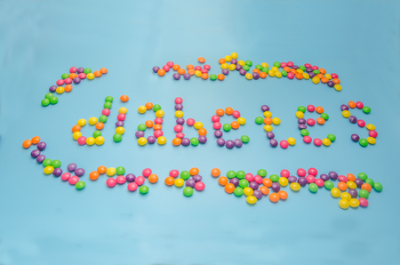 candy caramel lined word diabetes, on blue background, closeup