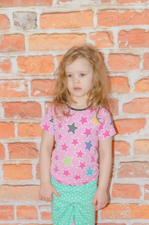 sad girl, child on brown brick wall background, loneliness, resentment, punishment