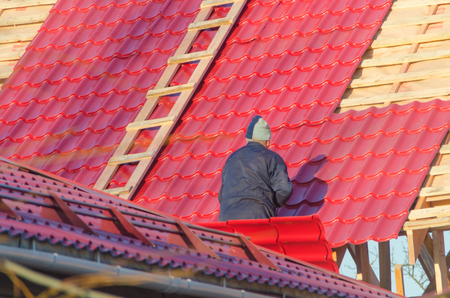 the man, the worker, the roofer covers a roof of the wooden, frame house with red metal tile, by means of the screwdriver