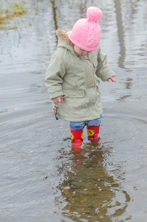 in early spring, the girl, a child in rubber boots standing in a large puddle with keys to the house in his hands Foto de archivo - 100965078