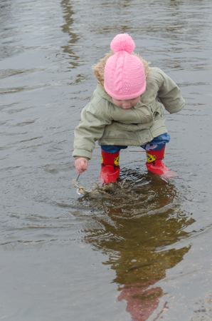 early spring girl, child in rubber boots standing in a large puddle of wet house keys Banque d'images - 100662485