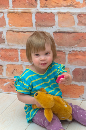 the little girl, the child gives, stretched out in a hand a pacifier.  fawn. on the background of red brick wall Фото со стока