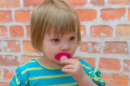 little girl, crying baby. pacifier. on the background of red brick wall