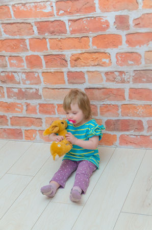 a little girl, a child with a pacifier and deer in hands on a background of red brick wall