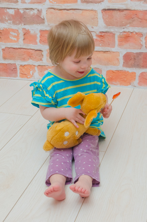 on the background of red brick wall, little girl, baby with candy on a stick feeding, treats the deer toy