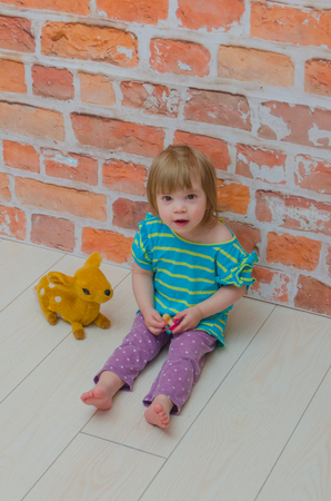 red brick wall background, little girl, baby with pacifier and toy deer Фото со стока