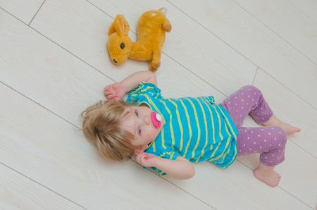 little girl, baby with pacifier lying on the floor on a toy deer