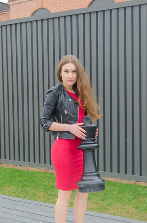 beautiful girl in red dress and leather jacket on a large chessboard with a black king figure in her hands