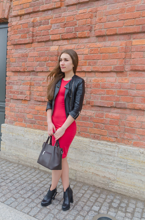 beautiful girl with bag in red dress and leather jacket on brick wall backgroun Stock Photo