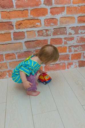 on the background of red brick wall the little girl, the child plays, rolls red car Фото со стока