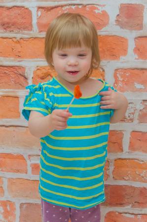 against a brick wall a little girl, a child eats caramel candy on a stick Stok Fotoğraf