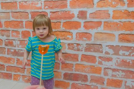 against a brick wall a little girl, a child eats caramel candy on a stick Фото со стока